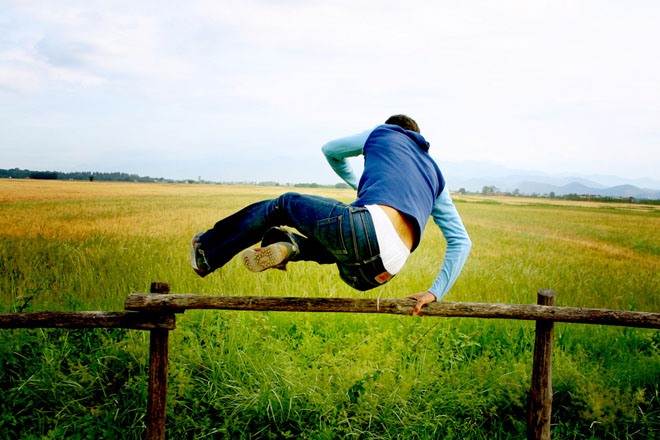 Person leaping over a wooden fence to represent change